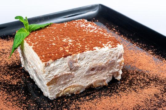 tiramisu cake on a black plate. tasty italian dessert decorated with mint