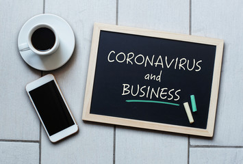 Coronavirus and Business text written on blackboard.
