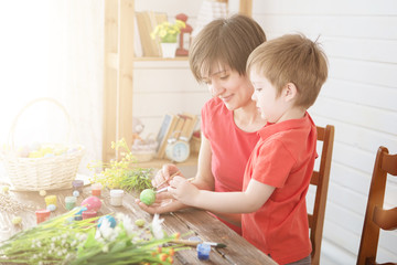 Easter preparations. Happy young mother spending time with her joyful son. Happy family Mom and children son paint easter eggs with colors. Preparation for holiday.