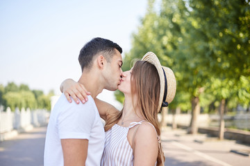 Handsome man, wearing white t-shirt, blue shorts, is kissing pretty woman in stripy summer overall. Close-up picture of young couple in love, embracing, looking at each other, smiling.