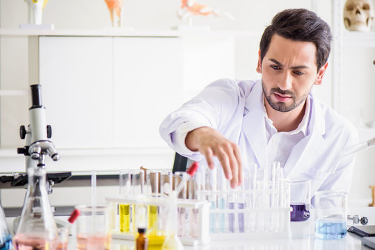 Attractive happiness scientist man lab technician assistant analyzing sample in test tube at laboratory. Medical, pharmaceutical and scientific research and development concept.