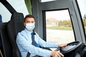 transport, travel and pandemic concept - male driver wearing protective medical mask for protection from virus disease driving intercity bus