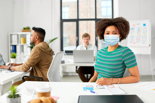 health, safety and pandemic concept - african american woman wearing protective medical mask for protection from virus at office