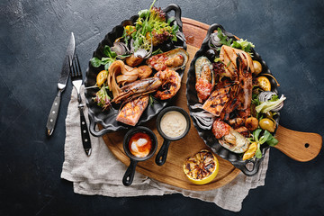 Assorted seafood on plates. Beautiful composition on a served seafood table, squid, shrimp, salmon steak and octopus. Food photo, low key, traditional Italian cuisine. Top view, save the space