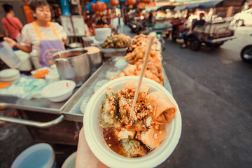 Bangkok street food court and small plate with spring rolls in hand of hungry customer. Asian snacks in time for lunch