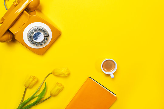 Yellow layout with retro rotary telephone, cup of coffee, flowers and notebook.