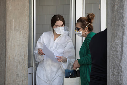 A medical worker in protective suits talks to a woman in front of the infection clinic, as the number of coronavirus (COVID-19) cases grow around the world, in Belgrade