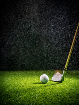 Beam of light in the rain illuminating a golf club and golf ball on the turf