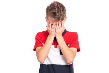 Poster - Portrait of teen boy with sad expression covering face with hands while crying. Upset caucasian young teenager, isolated on white background. Unhappy child crying, not showing his tears.