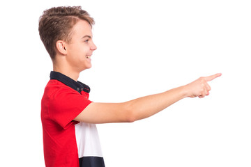 Fototapete - Portrait of teen boy pointing finger away at copyspace - side view, isolated on white background. Happy teenager smiling and pointing fingers at something. Cute child looking away - profile.
