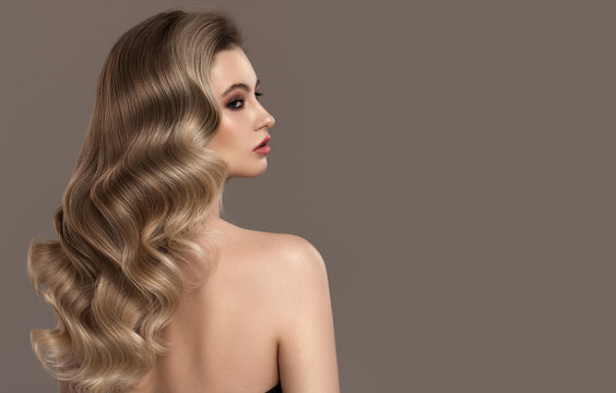 Portrait of young blonde woman. Long beautiful wavy hair.