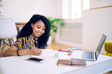 Smiling black teenager doing homework at home
