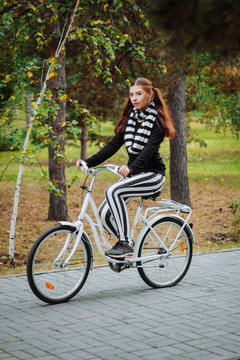 A young, attractive woman rides a white bike in the evening in an autumn park.