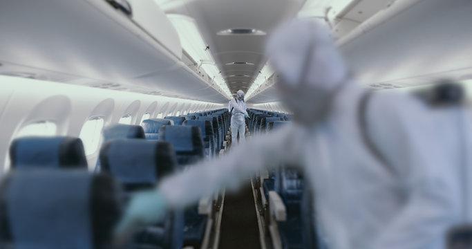 HazMat team in protective suits decontaminating airplane cabin during virus outbreak