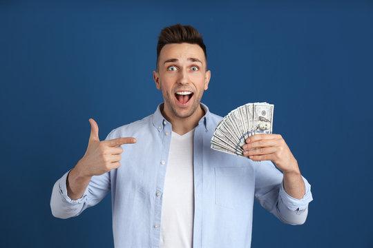 Emotional man with cash money on blue background