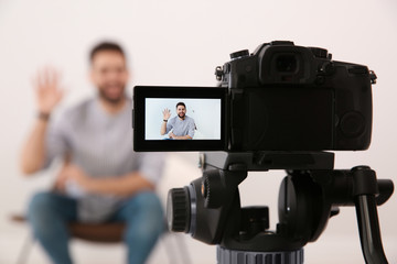 Young blogger recording video indoors, focus on camera screen
