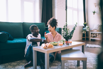 Multiracial couple eating strawberry while having romantic dinner at home Fototapete