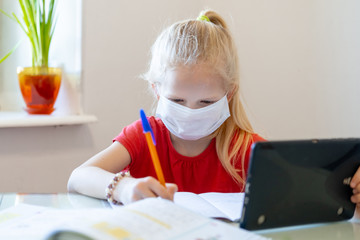 Distance learning online education. Sickness schoolgirl in medical mask studying at home with...