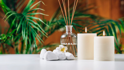 Aromatherapy Concept. Aromatic White Candles and Essential Oil Reed Diffusers