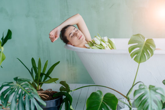 A relaxing bath. Young brunette woman holding bouquet of tulips in the bath on mint green background. With plant green pots around bathtub. Morning routine, hygiene, lifestyle concept.