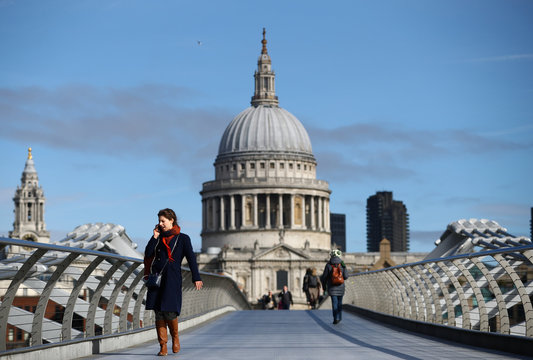 A woman walks across Millennium Bridge during rush hour, as the number of Coronavirus cases grow around the world, in London