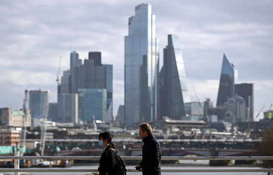 A woman wearing a protective mask walks across Waterloo Bridge in front of the City of London financial district during rush hour, as the number of Coronavirus cases grow around the world, in London