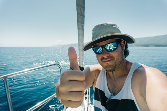 Man with hat and sunglasses showing thumb up at the bow of a sailboat. Sailing and yachting concept.