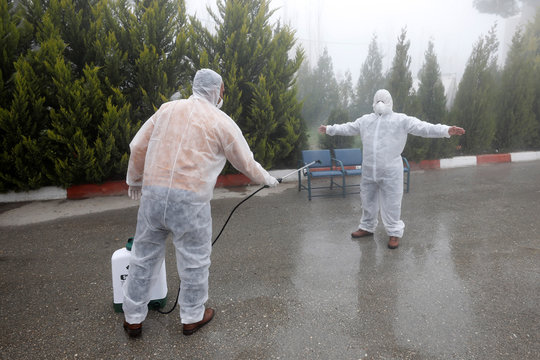 A member of a medical team sprays disinfectants to sanitize the suit of his colleague in a Red Crescent-run hospital which will be used for coronavirus quarantine, near Hebron in the Israeli-occupied West Bank