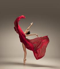 Free flight. Graceful classic ballerina dancing on grey studio background. Deep red cloth. The...