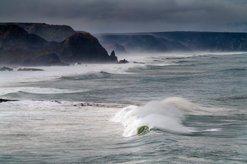 Scenic view of the coastline along the Amado Beach (Praia do Amado) with big waves during a storm, in Algarve, Portugal