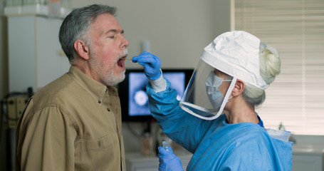 A mature Caucasian man in a clinical setting being swabbed by a healthcare worker in protective garb to determine if he has contracted the coronavirus or COVID-19..