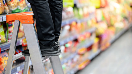 Male storekeeper legs standing on aluminum stair putting products on shelves in grocery store or supermarket. Worker filling foods stock for groceries business.