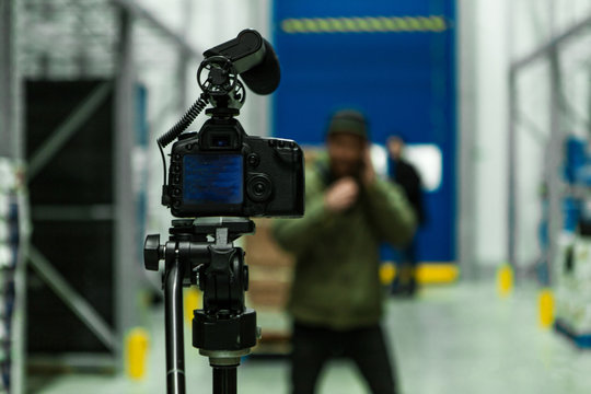 A close up selective focus shot of a professional DSLR camera and shotgun mic mounted on a tripod inside a warehouse, with blurry presenter in background.