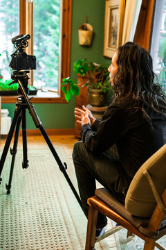 Closeup selective focus view of film maker sitting behind a professional DSLR camera on a tripod with shotgun microphone, filming documentary indoors.