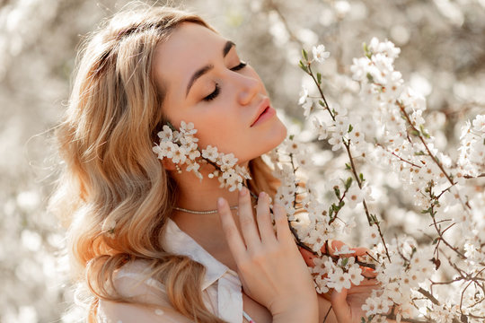 Pretty woman in spring blossom garden