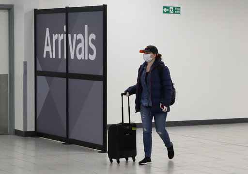A woman wearing a face mask walks through Luton Airport as the number of coronavirus cases grow around the world