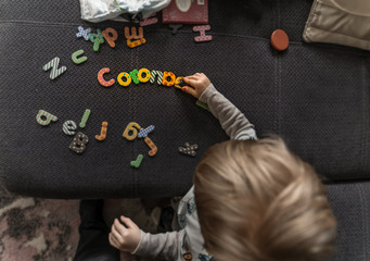 Home care for a little boy, while the kinder gardens are closed because of the Corona, Covid 19 threat, with letters Corona.