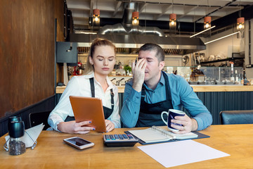 Worried business owners calculating finances - Small restaurant entrepreneurs SME go bankrupt due to Coronavirus pandemic - Young woman and man with headache and overwhelmed by financial difficulties
