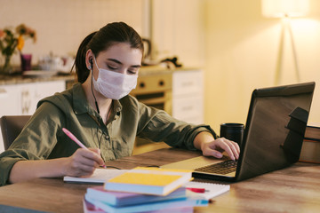 woman working at home with medical mask on face. coronavirus quarantine remote home working concept.