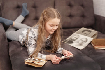 Young Girl sits on sofa and looking at old family photo album. Fotomurales