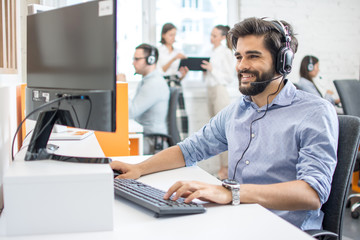 Smiling friendly helpline technical support agent with hands-free headset at call centre.