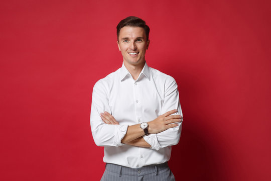 Attractive young business man in white shirt gray pants posing isolated on bright red background studio portrait. Achievement career wealth business concept. Mock up copy space. Holding hands crossed.