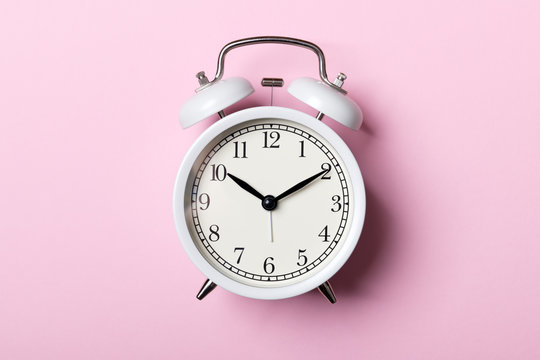 White vintage alarm clock on pink background. Time concept