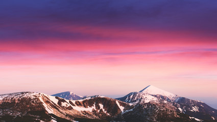 Tuinposter Aubergine Purple sunrise light glowing on snowy mountains peaks on background. Landscape photography