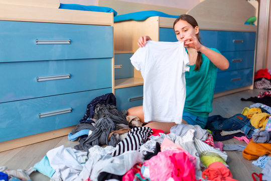 Beautiful teenage girl folding her messy clothes in a her bedroom