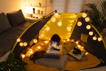 Little 11 year old girl using laptop under her home-made tent inside the living room.