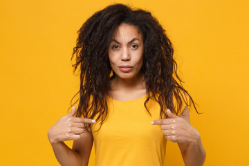 Perplexed confused young african american woman girl in casual t-shirt posing isolated on yellow orange background. People lifestyle concept. Mock up copy space. Pointing index fingers on herself.