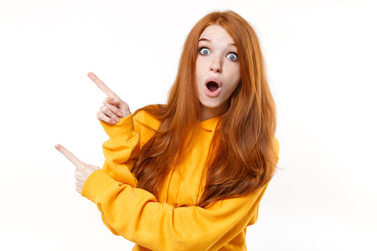 Shocked young redhead woman girl in casual yellow hoodie posing isolated on white background studio portrait. People emotions lifestyle concept. Mock up copy space. Pointing index fingers aside up.