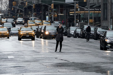 A woman takes photos of nearly deserted streets in Times Square following the outbreak of Coronavirus disease (COVID-19), in the Manhattan borough of New York City