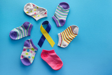 World Down syndrome day background. Down syndrome awareness concept. Socks and ribbon on blue...